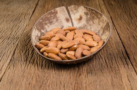 almond in wooden bowl on wooden board