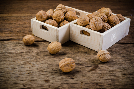walnuts in wooden crate on table