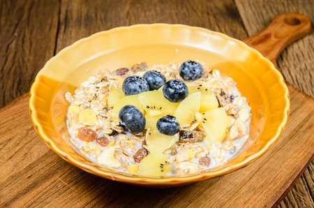 muesli cereal grain with blueberry and kiwi on wooden plate