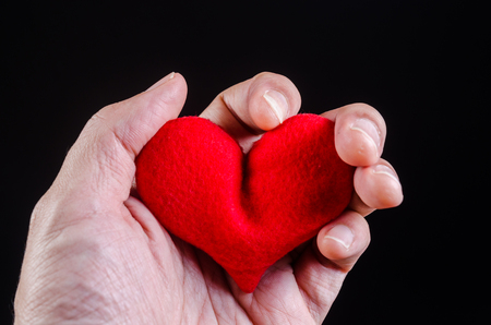 hand squeezing red heart with anger and Suffering from heart attack , love problem concept