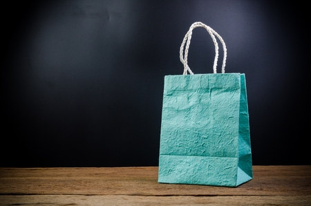 paper shopping bag on wooden board Stockfoto
