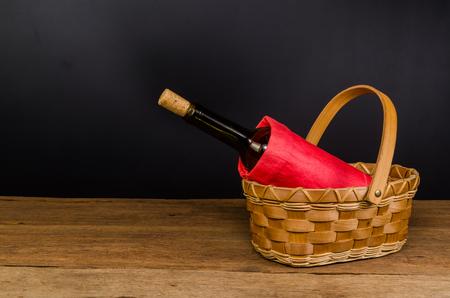 red wine bottles on wicker basket on wooden board and black background Stockfoto