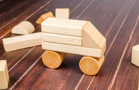 Car from wooden toy blocks on wooden board background, concept image Stockfoto