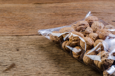 walnuts in plastic bag package on wooden table