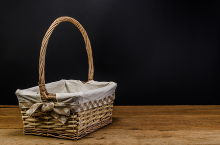 wicker basket on wooden board and black background