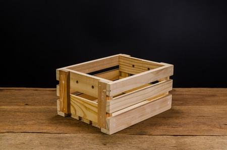 empty wooden crate on wooden board and black background