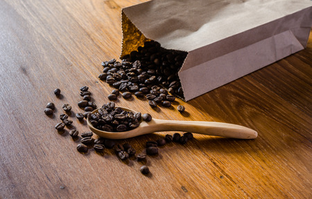 roasted coffee beans from paper bag on wooden board background