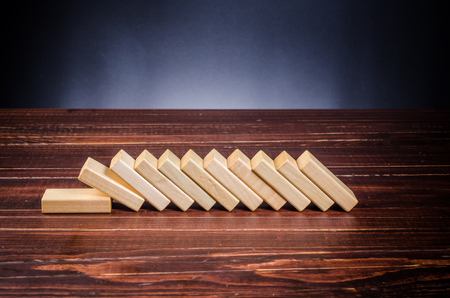 Wooden blocks shape toy on wooden board background,domino effect in business concept Stockfoto