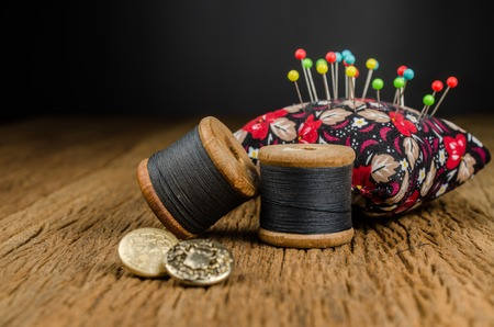 vintage wooden spool thread with pincushion on wooden board