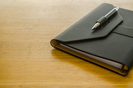 black leather organizer with pen on wooden table