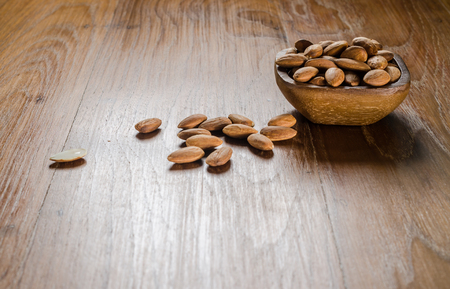heap of almond from wooden bowl on wooden board