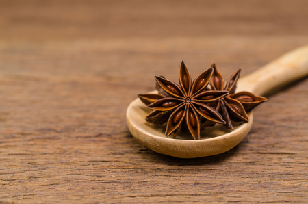 Star anise in wooden spoon on wooden board background,Chinese star aniseed