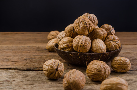 Heap of walnuts in coconut shell on wooden table