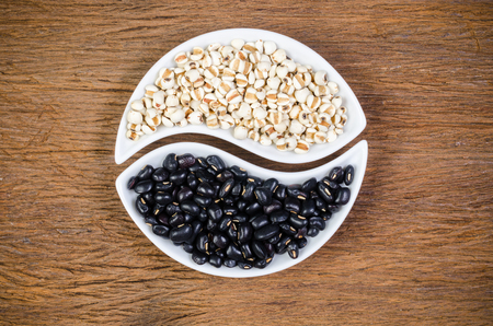 Job's tears and black beans in ying yang porcelain shape on wooden board with wooden board background, agriculture products Stockfoto