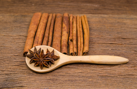 Star anise on wooden spoon and cinnamon stick on wooden board background,Chinese star aniseed