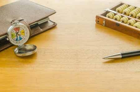 Compass and brown leather organizer with abacus on wooden table,key to success concept image