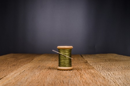 vintage wooden spool thread with needle on wooden board