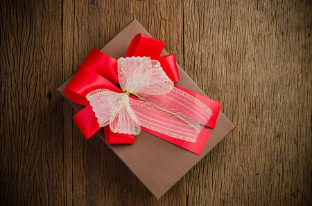 Brown gift box with white and red bow on wooden board background Stockfoto