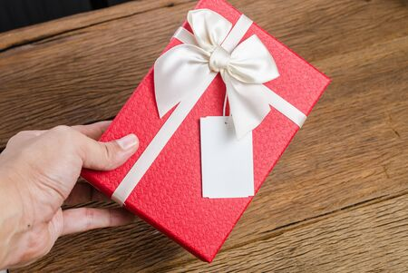 Red gift box with white bow with tag on wooden board background