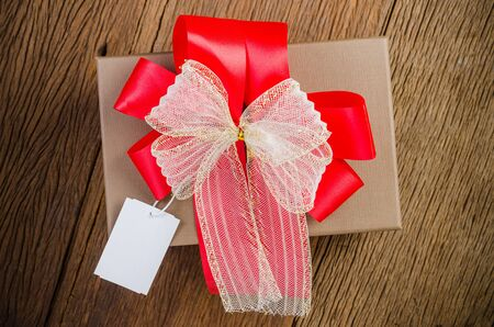 brown gift box with white bow with tag on wooden board background Stockfoto