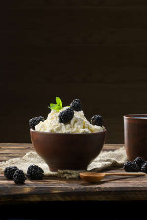 Dairy product cottage cheese and milk in brown ceramic bowl with spoon on wooden table