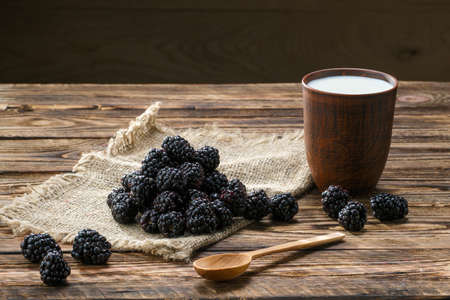 Heap of fresh dewberry on sackcloth table-napkin and clay cup with milk on wooden table