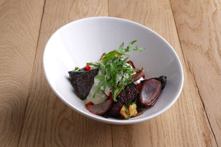 Autumn hot salad with deep fried beetroot, onion, tomato and nuts Фото со стока