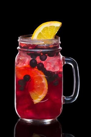 Cocktail with black currant and vodka in mason jar mug isolated on black Stock Photo