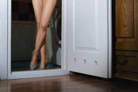 Nackte weibliche Beine in der Tür des Badezimmers