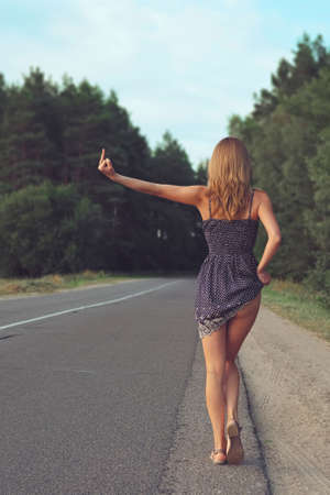 Pretty girl in short dress on the road showing middle finger. Stock Photo