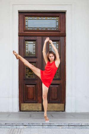 Full length portrait of pretty girl in short dress lifting her leg up