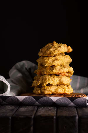 Low key photo of  stack of of ginger, lemon and apple biscuits on wooden table. Chocolate chip cookies on dark wooden background with copy space.