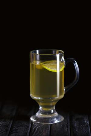 Low key photo of glass of lemon tea on wooden table Stock Photo