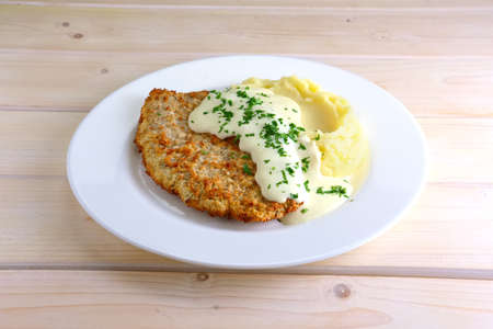 Chopped cutlet in breading with mashed potato and cream sauce Stock Photo