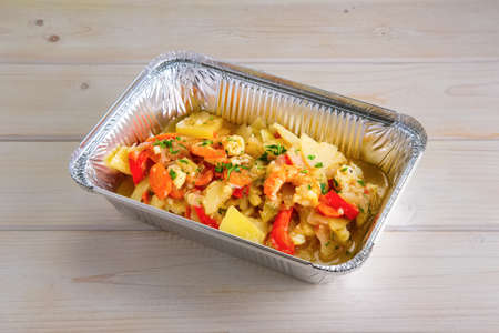 Shrimp stew with potato, paprika, carrot and onion in take away packing Imagens