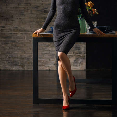 Beautiful bare female legs in red patent leather shoes bent knee and leaning on the table