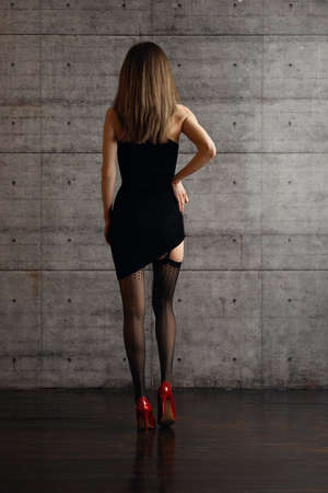 Back view of beautiful lady lifting fitting dress and showing legs in black stockings with belt