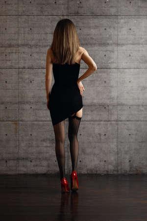 Vue arrière de la belle dame soulevant une robe ajustée et montrant les jambes en bas noirs avec ceinture