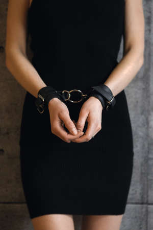 Close up view of female hands in black leather handcuffs