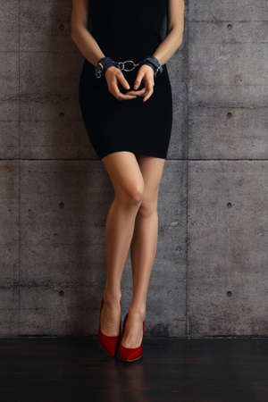Unrecognizable girl in black dress and leather handcuffs Stok Fotoğraf