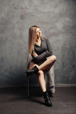 Pretty size plus model sitting on chair near grunge abstract wall on background in closed body and rough boots