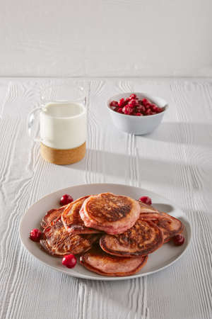 Pancakes with cherry and glass of milk on white kitchen table Banco de Imagens