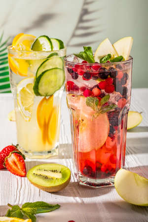 Variations of lemonades with different fruits and syrups on wooden table under morning sun