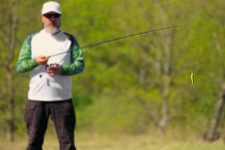 Selective focus photo of fisherman with spinning rod and focus at artificial lure