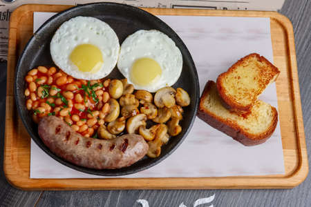 Iron hot plate with fried eggs, sausage, mushroom and kidney beans with toasted bred 版權商用圖片