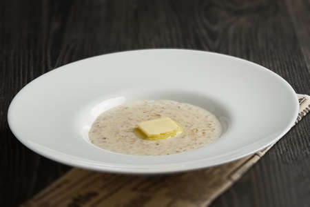 Plate of liquid oatmeal with piece of butter on wooden table