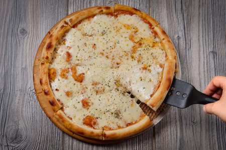 Cutted cheese pizza on wooden table. Top point of view.