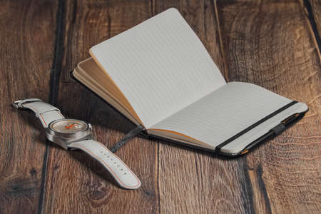 Open blank notebook with pen and wrist watch on wooden table.