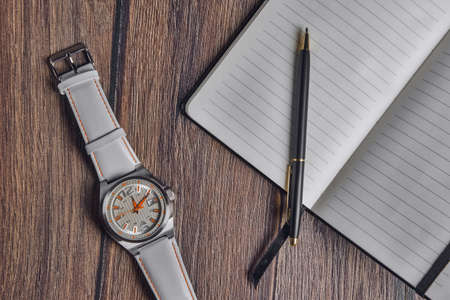 Top view of open blank notebook with pen and wrist watch on wooden table.