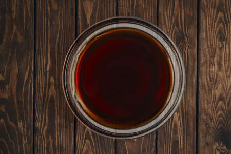 Top view of plate with soy sauce on wooden table